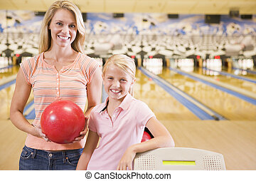 Woman and young girl in bowling alley holding ball and...