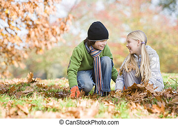 Two young children outdoors in park playing in leaves and smiling (selective focus)