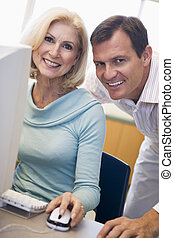 Man and woman at computer smiling (high key)