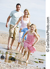 Family running at beach smiling