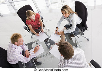 Four businesspeople in a boardroom with paperwork