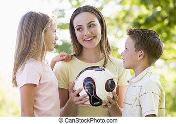 Woman and two young children outdoors holding volleyball and...