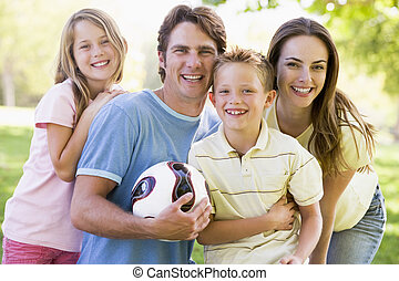 Family standing outdoors holding volleyball smiling