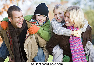Parents outdoors piggybacking two young children and smiling...