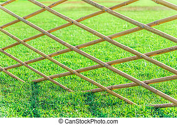 Crossed bamboo fence with green grass in the garden7