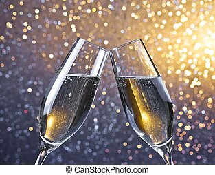 cheers with two champagne flutes with golden bubbles on...