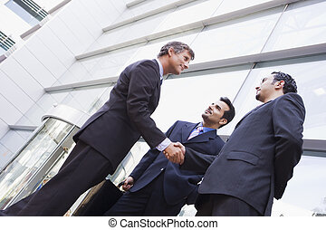 Three businessmen outdoors by building shaking hands and...