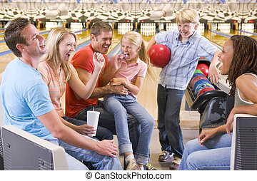 Family in bowling alley with two friends cheering and...