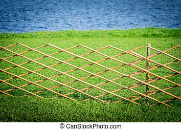 Crossed bamboo fence with green grass in the garden5