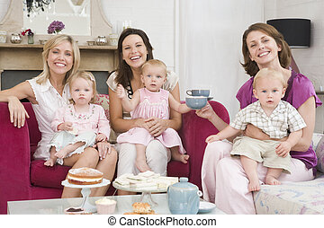 Three mothers in living room with babies and coffee smiling