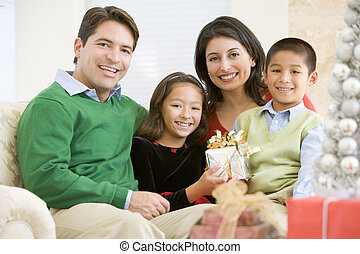 Family Sitting On Sofa Together,Holding A Christmas Gift