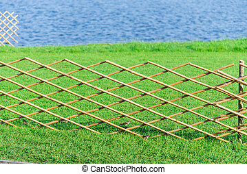 Crossed bamboo fence with green grass in the garden4
