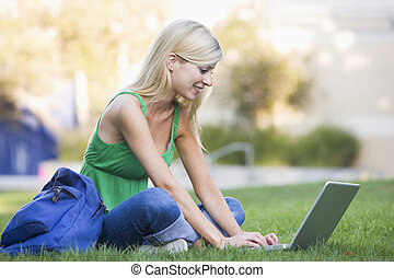 Woman outdoors sitting on grass with laptop selective focus...
