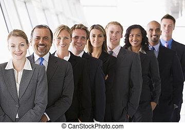 Group of co-workers standing in office space smiling (high key/depth of field)