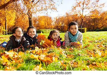 Four kids lay in autumn leaves - Group of four black boys...