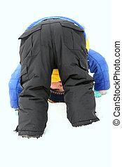 Toddler in snowsuit bending over in winter snow