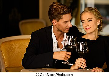 Beautiful young couple with glasses of wine in luxury...