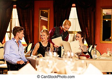 Group of young friends with choosing in a luxury restaurant