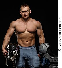 Man with naked muscular torso holding american football...