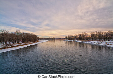 Dusk on the Bow River in winter with pink tones in the sky
