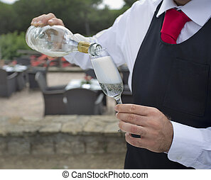 waiter pouring a glass of wine or champagne outside - focus...