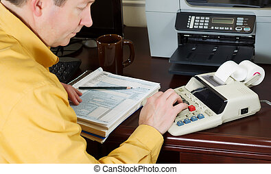 Mature man working the numbers on his income taxes -...
