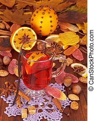 Glass of mulled wine and orange on background