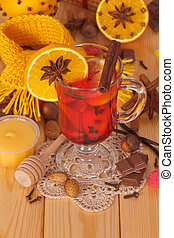 Glass of mulled wine with scarf on wooden table