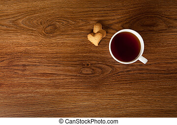 hot cup of tea with cookies on wooden table