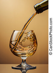 Cognac pouring from bottle into glass with splash on brown...