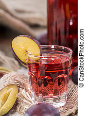Plum Liqueur in small glasses with fresh fruits