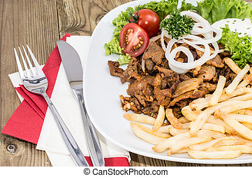 Portion of Kebab meat on a plate on wooden background