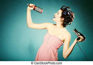 sexy girl in curlers with hairdryer styling hair - young...