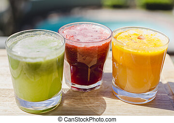 Yellow, green and red fruit and vegetable juices in tumbler...