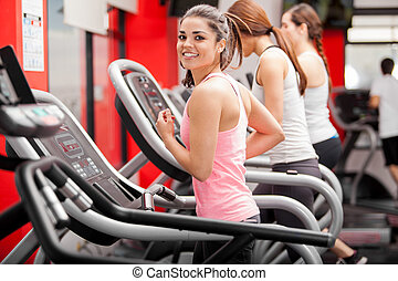 Exercising on a treadmill - Pretty girl working out in a...