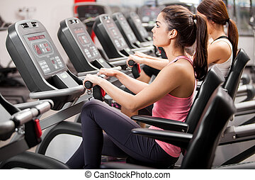 Spinning session at the gym - Group of young Latin women...