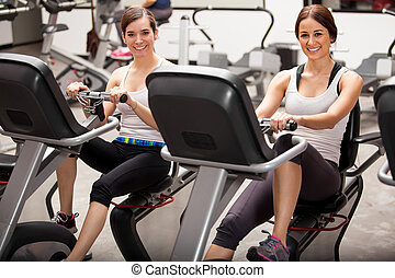 Best friends in spinning class - Happy female friends...