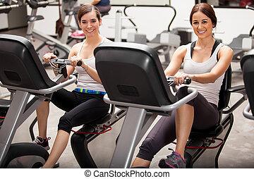 Best friends in spinning class - Happy female friends...
