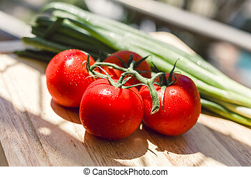 Fresh juicy tomatoes on wooden chopping board - Vibrant red...