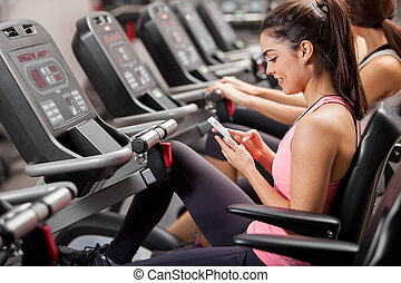 Sending a text during gym class - Athletic young brunette...