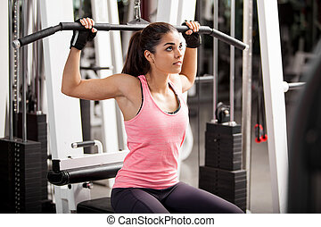 Building muscles at the gym - Cute Hispanic woman toning her...
