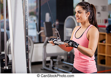 Toning my muscles at the gym - Pretty young woman using a...