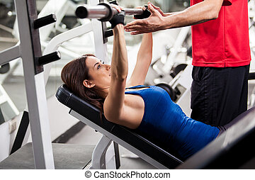 Working out with my instructor - Cute young woman lifting a...