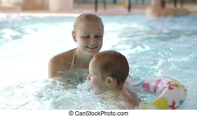 Little child having swimming lessons in a swimming pool with...