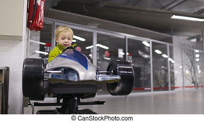 Little boy driving a racing car - Little boy enjoying...