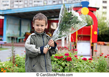 Little boy 3-4 years old with flowers