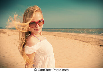 Romantic girl dreaming at sea coastYoung woman in summer...