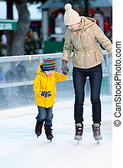 family ice skating - happy smiling mother and her cute...