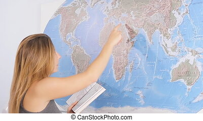 woman planning a trip - woman looks world map with a guide...