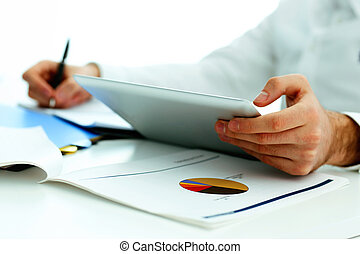 Closeup image of a man holding tablet computer and writing...